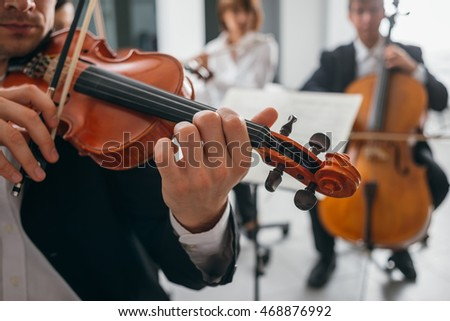 Violinist performing on stage with classical music symphony orchestra, hands close up, selective focus, unrecognizable people