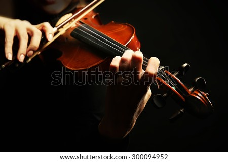 Violinist playing violin on dark background - stock photo