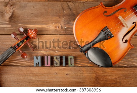 violins in wood background and word music in letterpress type - stock photo