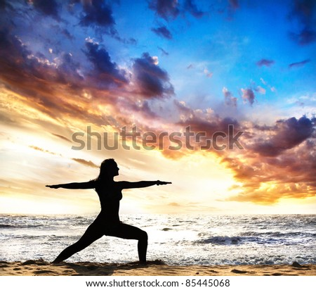 virabhadrasana II warrior pose by beautiful Woman silhouette on the sand beach and ocean nearby at sunset background in India, Goa - stock photo