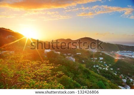 Virgin Islands St Thomas sunrise with colorful cloud, buildings and beach coastline. - stock photo