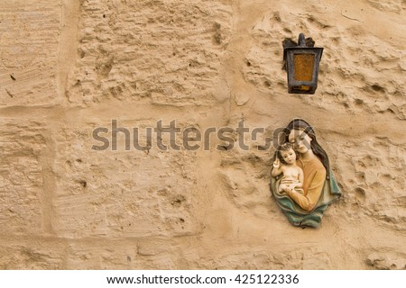 Virgin Mary and a child Small statue of Virgin Mary and a Child under a lantern on a texture wall of a house at the mediterranean island Malta.  - stock photo