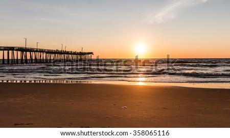 Virginia Beach, Virginia boardwalk fishing pier with the sun at the horizon. - stock photo