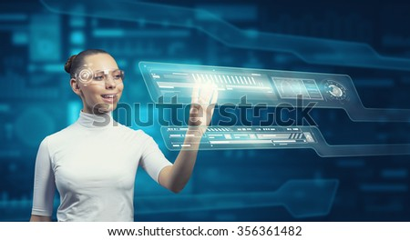 Virtual holographic interface used by young pretty woman  - stock photo