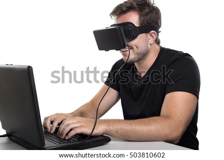 Virtual Reality gamer wearing headset tethered to a gaming pc.  The man is either playing video games or a developer beta testing a VR app.