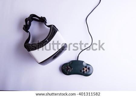 Virtual reality goggles and gamepad on table, studio shot - stock photo