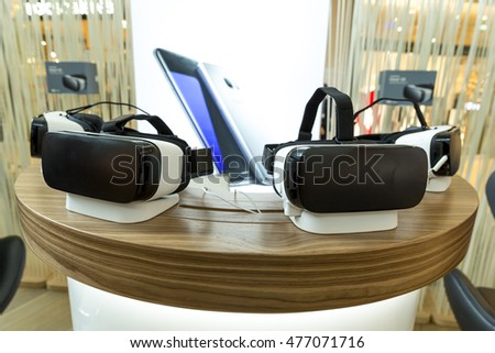 Virtual reality (VR) headsets (glasses) on a table. VR is immersive multimedia or computer-simulated reality - a computer technology that replicates an environment.
