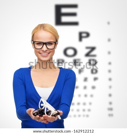 vision and health concept - smiling woman in casual clothes wearing and holding eyeglasses - stock photo
