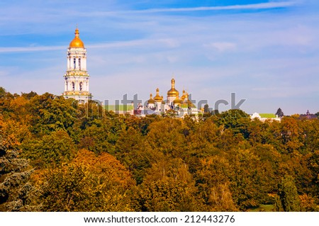 Vision of the Pechersk Lavra Tower Bell behing the forest during a sunny autumn day with clouds in the blue sky - stock photo