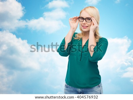 vision, optics, education and people concept - smiling young woman with eyeglasses over blue sky and clouds background - stock photo