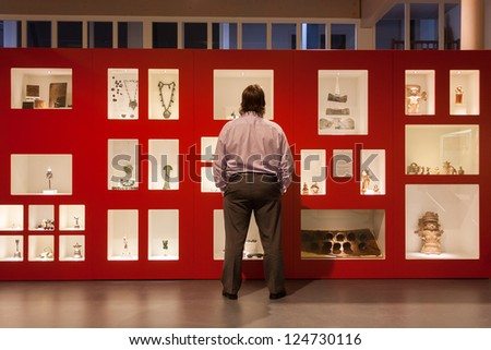 Visitor in a museum looking at relics in a display - stock photo