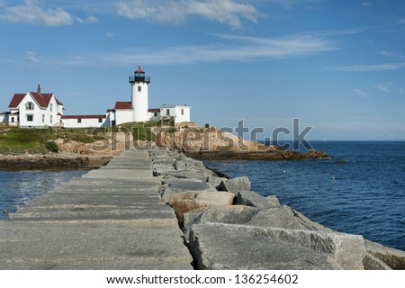 Visitors can walk along the nearly mile long jetty to get a clear view of Eastern Point Lighthouse in Gloucester, Massachusetts. - stock photo