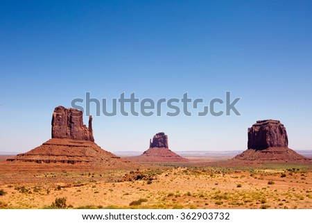 Visitors off in the distance view the mesas of Monument Valley Navajo Tribal Park in southern Utah, USA. - stock photo