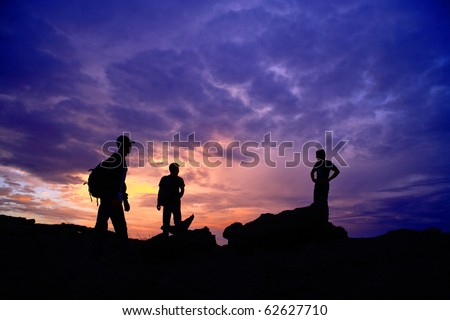 Visitors on the hill at sunset. - stock photo