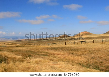 Vista of Wyoming landscape against blue sky, clouds, mountains. - stock photo
