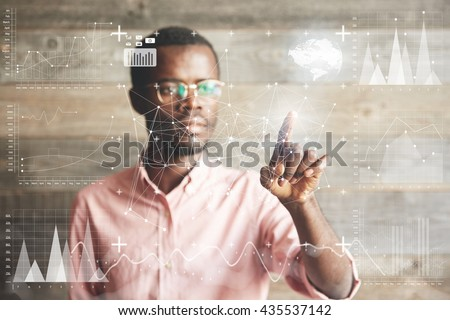 Visual effects. Future technology touch screen interface. Handsome African American businessman in shirt touching screen interface, drawing a chart in futuristic office. Selective focus on the hand - stock photo
