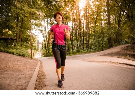 Vital senior woman jogging in park at sunset