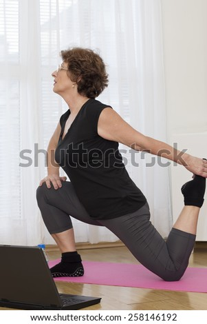 Vitality senior brown haired woman   exercise using a laptop at home.  - stock photo