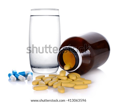 Vitamin C and pill is poured out of the bottle with glass of water on white background - stock photo