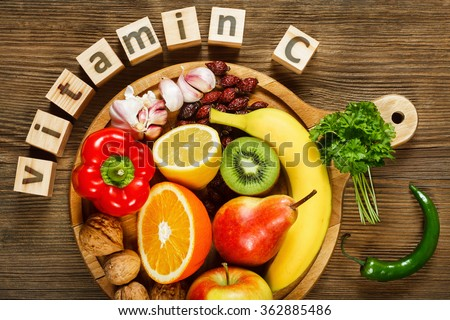 Vitamin C in fruits and vegetables. Natural products rich in vitamin C as oranges, lemons, dried fruits rose, red pepper, kiwi, parsley leaves, garlic, bananas, pears, apples, walnuts, chili. - stock photo