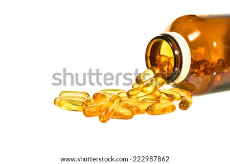 Vitamin D bottle with spilled contents isolated on white background - stock photo