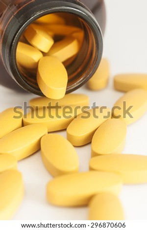 Vitamin spilling out of a bottle on white background, Vitamin pill spilling out of a bottle, Medicine capsule for health and capsule for life, Pill capsule with bottle on white