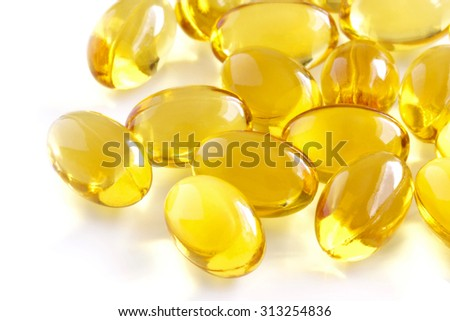 Vitamin supplement capsules closeup on a white background.