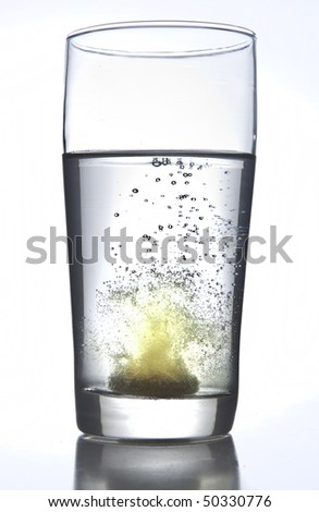Vitamin tablet dissolving in water - stock photo