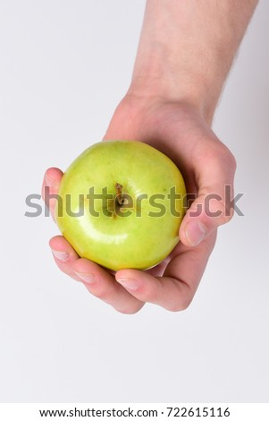Vitamins and fitness concept. Apple placed on white background. Male hand holds light green apple in palm. Apple in fresh and juicy color, close up