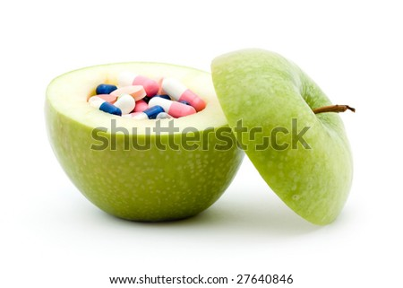 vitamins concept - apple and pills inside it studio isolated - stock photo