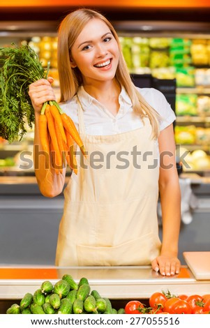 Vitamins for the customers. Cheerful young female seller smiling at camera and holding carrots while standing at a food store - stock photo