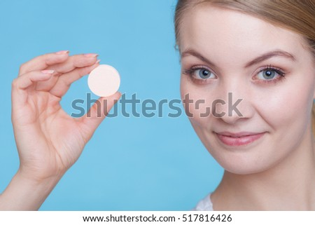 Vitamins, health, medicines. Woman holding behing her face big supplement effervescent tablet packed in tin foil, studio shot on blue background.