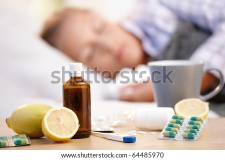 Vitamins, medicines and hot tea in front, woman caught cold sleeping in background.?