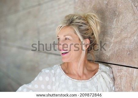 Vivacious beautiful blond woman posing leaning against a receding wall as she looks to the left with a laughing smile - stock photo