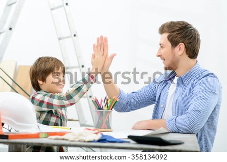 Vivacious father and son making renovation  - stock photo