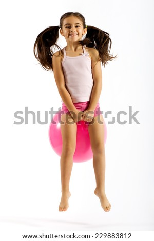 Vivacious little girl on a bouncing ball playing happily with a beaming smile and her pigtails flying up in the air as she bounces along, isolated on white - stock photo