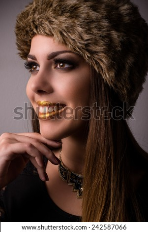 Vivacious smiling winter fashion model in a fur hat and knitwear looking to the side with her hand to her chin, close up face portrait - stock photo