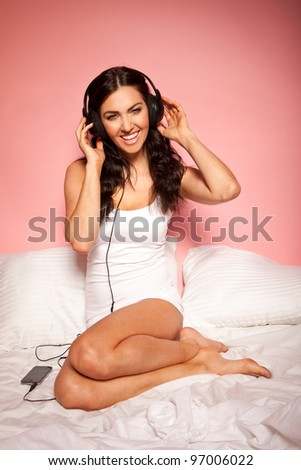 Vivacious woman curled up on her bed wearing headphones and listening to music - stock photo