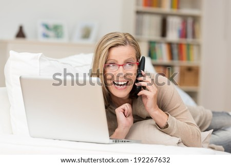 Vivacious woman laughing as she chats on her mobile phone while relaxing at home with a laptop computer - stock photo