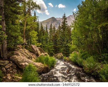 Vivid blue sky, mountains, and a flowing stream at Rocky Mountain National Park (RMNP), Colorado - stock photo