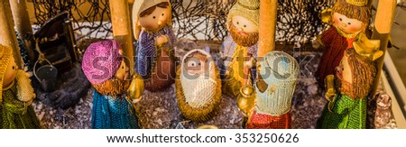 vivid colors of a Christmas Nativity scene, the Blessed Virgin Mary and Saint Joseph watch over the Holy Child Jesus in a manger while the wise men are bearing gifts - stock photo