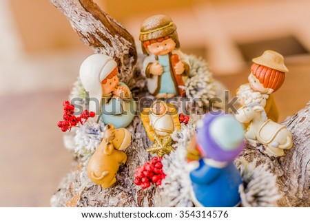vivid colors of a Christmas Nativity scene, the Blessed Virgin Mary and Saint Joseph watch over the Holy Child Jesus in a manger as the ox and the donkey are warming - stock photo