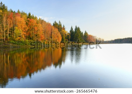 Vivid Colors of Fall Trees Reflecting in Lake - stock photo