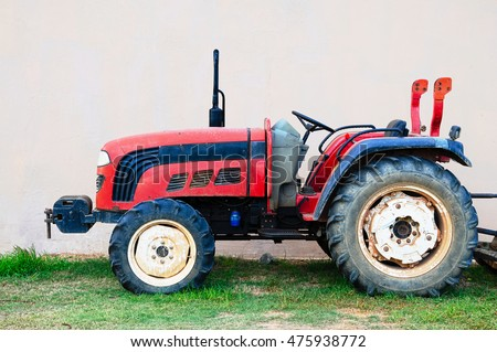 Vivid red old broken tractor on plain background