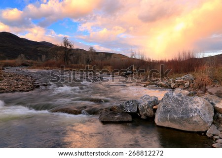 Vivid sunset sky above the Provo River, Utah, USA. - stock photo