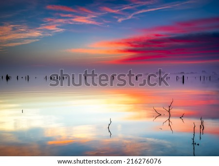 Vivid Texas sunrise over Benbrook Lake with colorful pastel reflections on the calm water - stock photo