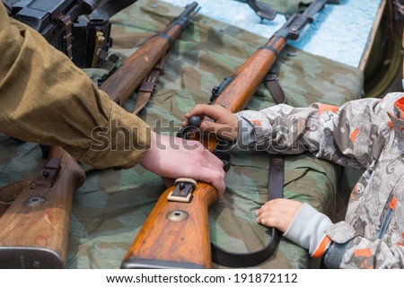 VLADIVOSTOK, RUSSIA - MAY 9, 2014: Children inspect weapons since World War II during festivities devoted to Victory Day. - stock photo
