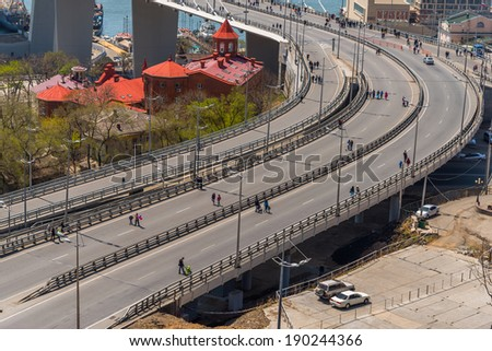 "VLADIVOSTOK, RUSSIA - MAY 1, 2014: Citizens walk on ""Golden Bridge"" in International Workers' Day event.  International Workers' Day is a celebration of labour and the working classes."