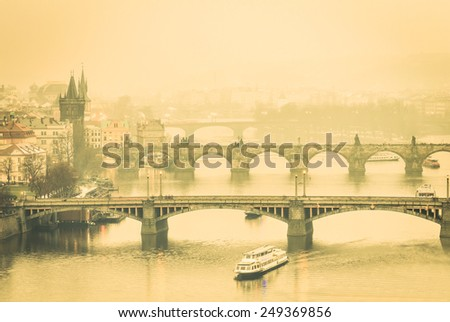 Vltava river and Charles Bridge from Letna Hill in Prague - World famous european capital of Czech Republic - Image edited with warm desaturated filtered look with soft focus due to the misty haze - stock photo