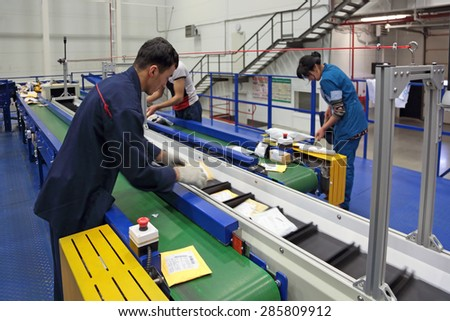 VNUKOVO, MOSCOW REGION, RUSSIA - APR 7, 2015: Russian Post. Logistics center in Vnukovo, working around sorting conveyor - stock photo
